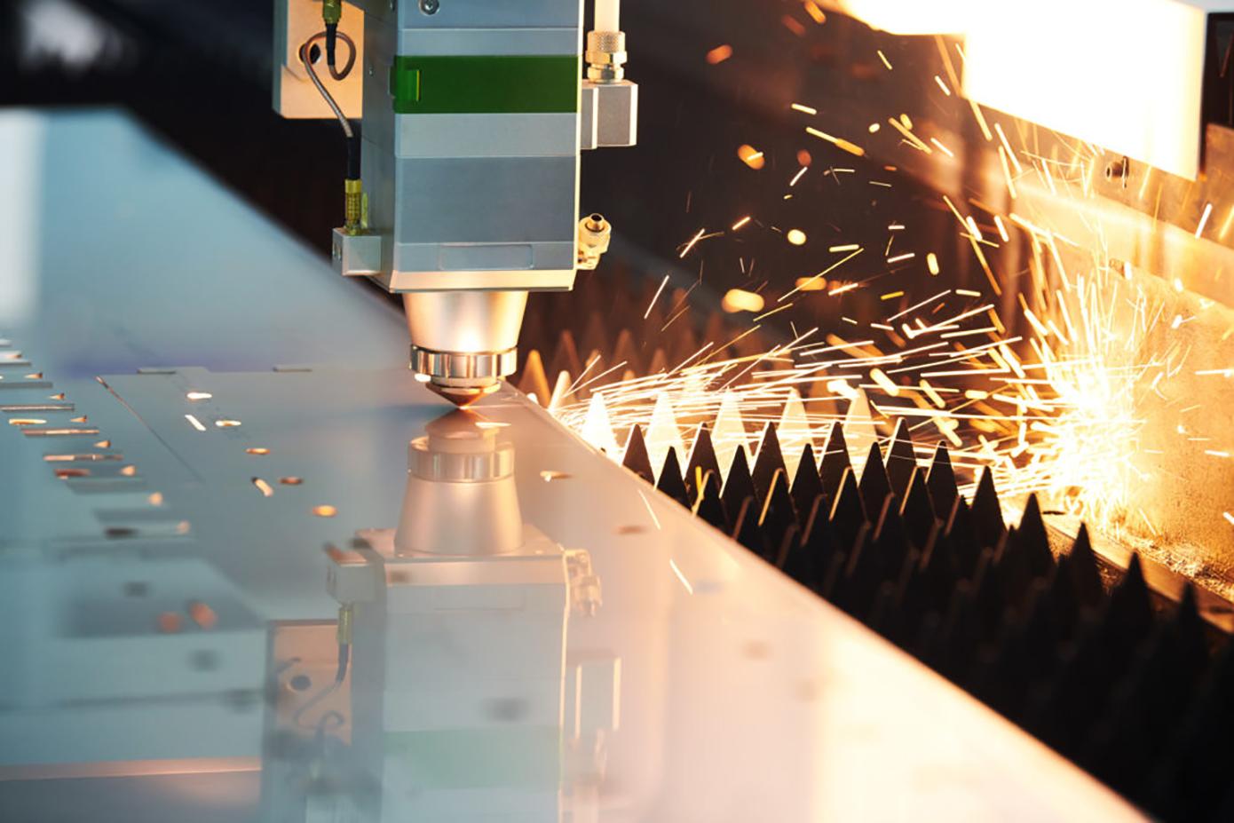 Laser cutting. Metal machining with sparks on CNC laser engraving maching